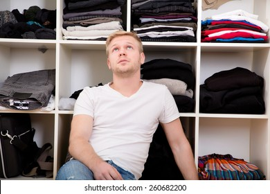 Young man sitting in front of his wardrobe.