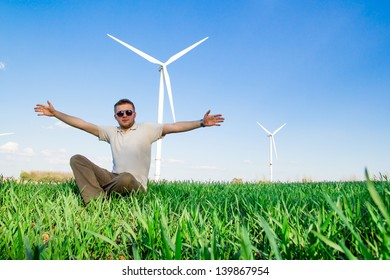 Young man sitting in front of windmill and the blue sky