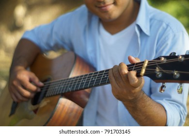 Young man sitting guitar in the garden happily.