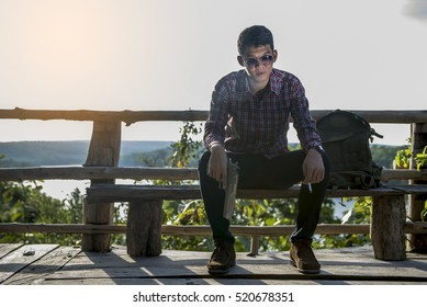 A young man sitting Hand holding a gun and smoking. hot sun