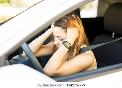 Young man sitting in her car with hands on head during traffic jam