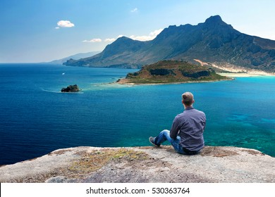 Young Man Sitting High on Mountain Ledge and Enjoying the View