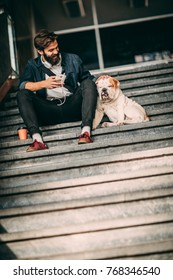 Young man sitting with his best friend on stairs in city. Handsome guy with his bulldog.