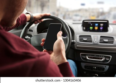 The young man sitting in his car behind the wheel and looking on his phone in his hand