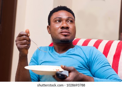 young man sitting holding a plate containing spaghetti