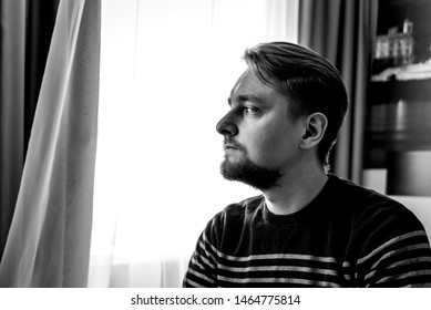 a young man sitting at home alone.a thoughtful man looks away. black and white photo