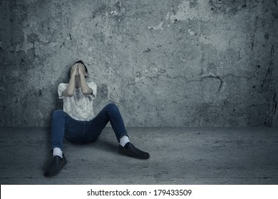 Young man sitting and leans on wall with fear