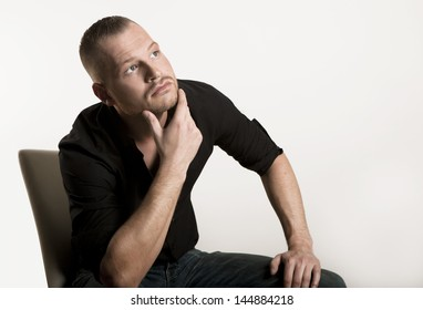 young man sitting looking up, white background, thinks, optional