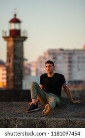 Young man sitting near the sea lighthouse on the promenade at sunset time.