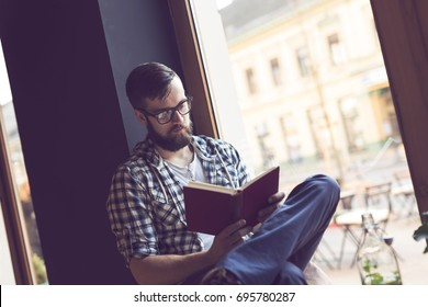 Young man sitting next to a window in a cafe, reading a book and enjoying his leisure time