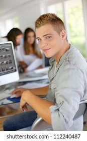 Young man sitting in office in front of desktop computer