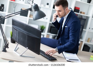 A young man is sitting in the office on the desk, talking on the phone and working with a computer.