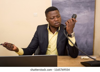 young man sitting in office suit with handset in angry hand.