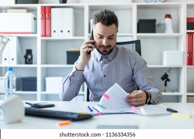 A young man is sitting in the office, talking on the phone and working with documents.