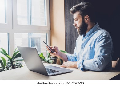 Young man sitting in office and using laptop and smartphone for work. Male person calling on mobile phone at workplace. Guy checking social accounts and email, sending text messages and commenting.