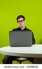 Young man sitting in the office and working on the laptop