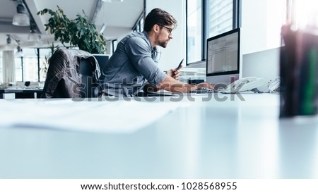 Young man sitting in office and working on desktop pc. Businessman looking at computer monitor while working in office.