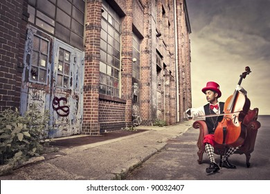 Young man sitting on an armchair on a city street and playing the cello