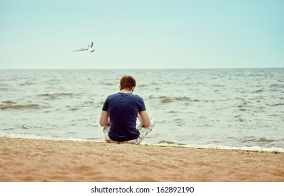 a young man sitting on the beach alone