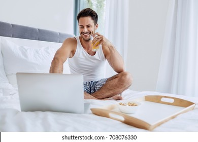 Young man sitting on bed and looking at laptop while drinking glass of orange juice and eating breakfast