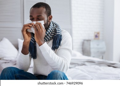 Young man sitting on the bed and blowing his nose