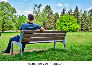 Young man sitting on bench and relaxing and thinking. Young guy lonely sitting on bench in park.