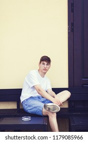 Young man sitting on a bench wear white t-shirt