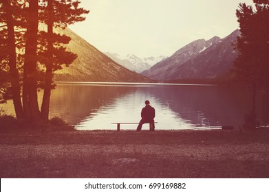 young man sitting on bench under lone tree. front of her have sunset time and like are background. this image for nature and lanscape