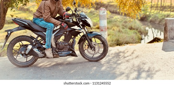 Young man sitting on a bike wearing jeans and shoes isolated unique photo