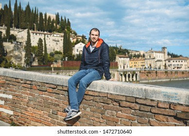 young man sitting on brick fence of bridge in Italy