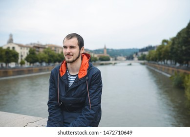 young man sitting on bridge over river