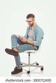 Young man sitting on chair and using mobile phone. Startupper. Young entrepreneur.