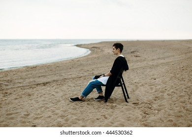 young man sitting on chair on the coast