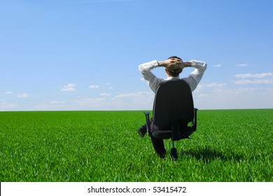 Young man sitting on chair on meadow with green grass