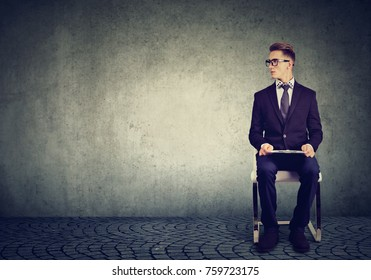 Young man sitting on a chair waiting for job interview