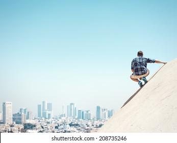 Jeune homme assis sur une falaise et une ville