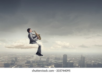 Young man sitting on cloud playing saxophone