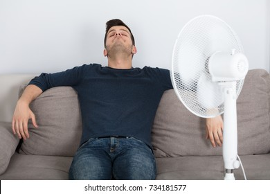 Young Man Sitting On Couch Cooling Off With Fan During Hot Weather At Home