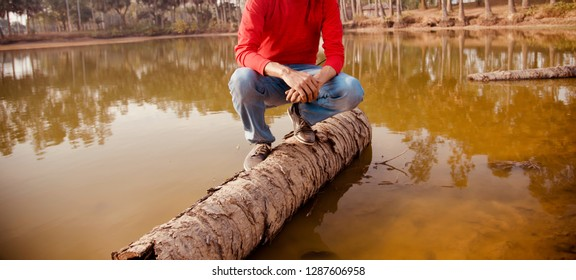 Young man sitting on a dead dried palm tree in the water