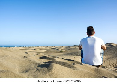 Young man sitting on a dune