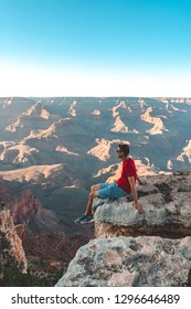 Young man sitting on the edge of the Grand Canyon in USA watching sunset.