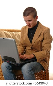 A young man sitting on the edge of a chair working on a laptop computer