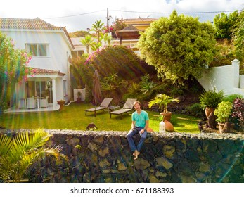 Young man sitting on the edge of the cliff by the villa on Tenerife island, Spain.