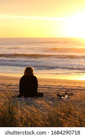 Young man sitting on an empty beach with his skateboard watching an intense sun rise over the ocean as waves break.