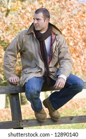 Young man sitting on fence with autumn leaves in background