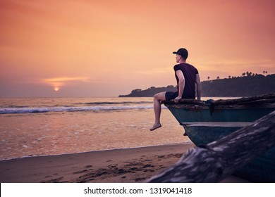 Young man sitting on fishing boat at sunrise. Contemplation on idyllic sand beach near Tangalle in Sri Lanka.