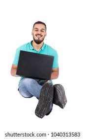 A young man sitting on the floor spread his legs forwardly and crossed it with his laptop, isolated on a white background.