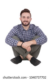 A young man sitting on the floor with a crossed legs smiling. holding his wrist, isolated on a white background.