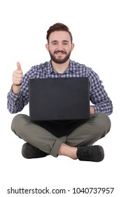 A young man sitting on the floor crossed legs with his laptop thumbs up, isolated on a white background.