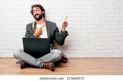 young man sitting on the floor smiling and pointing to the side with both hands, towards the place where the publicist may show a concept.